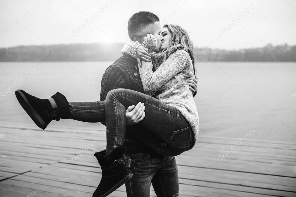 Парень держит девушку на руках и целует